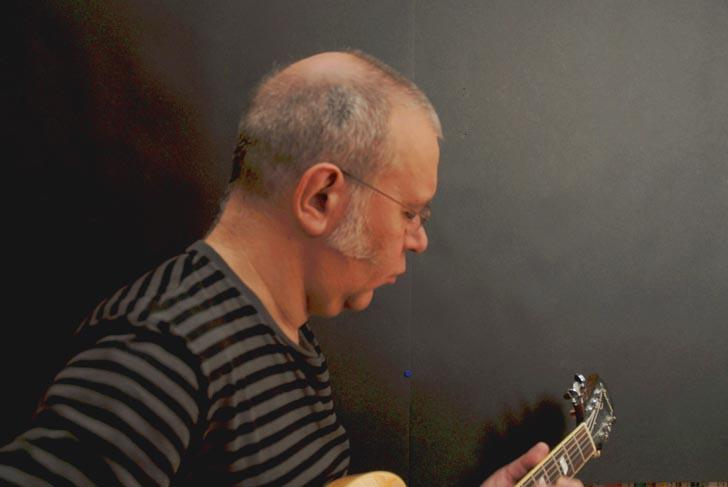 Hugo tocando su guitarra de perfil